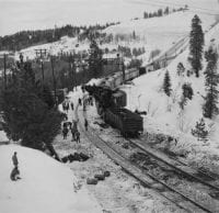 A Southern Pacific work train and wrecker crane cleans up a train wreck at Emigrant Gap in Automatic Train Stop territory. [No. 1], January 1965, DeGolyer Library, SMU