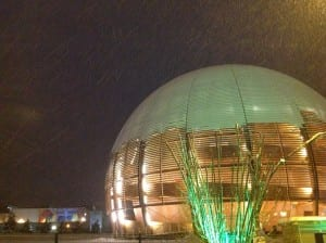 The CERN Globe, partially covered in snow, as more snow falls. The ATLAS Control Room building is seen in the distance.