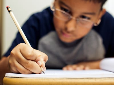 Stock photo of child writing in a notebook