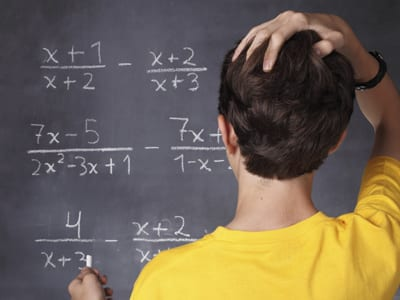 Stock photo of a student working a math problem on a blackboard