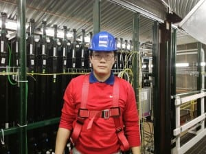 SMU graduate student Biao Wang is 300 feet underground in front of the close detector. Under the direction of SMU physicist Thomas Coan, Wang works on the maintenance and trouble shooting of the detector as an on-call expert for the cooling system of the read-out electronics.