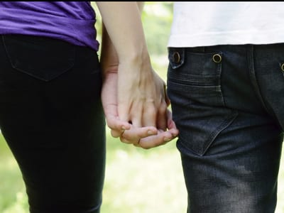 Stock photo of two people holding hands