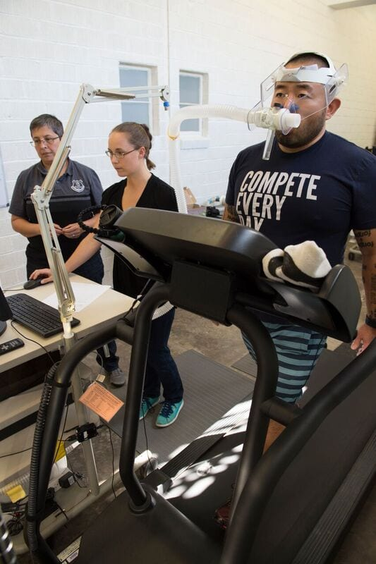 Jennifer Nollkamper and Dr. Lindsay Ludlow assist Dr. Takeshi Fujii in a treadmill test that captures volume of oxygen, volume of expired air and the levels of oxygen and carbon dioxide, all variables that help measure energy expenditure during walking. (Hillsman Jackson, SMU)