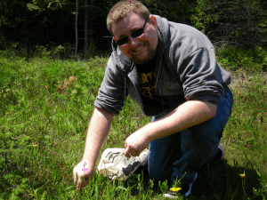 Zachary Gates collecting soil near Grass Pink orchids at the Ridges Sanctuary.