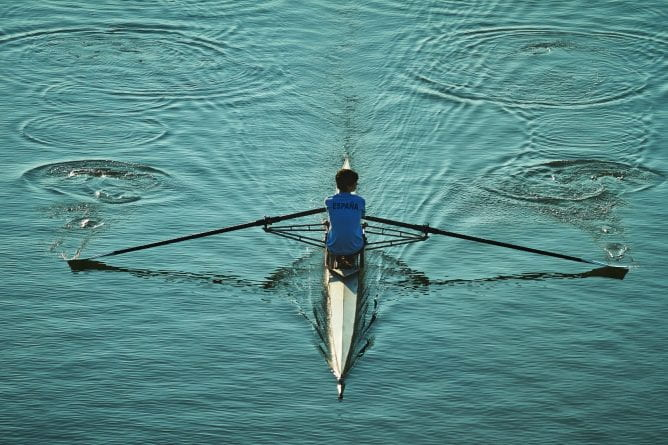 Person rowing a small boat on calm waters