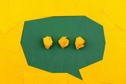 A chat bubble made of yellow note cards