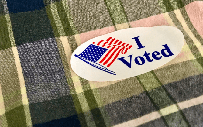 """An """"I Voted"""" sticker on green plaid fabric."""