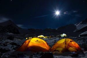 Tents illuminated from within on a dark night.