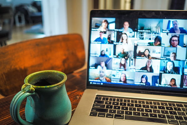 A coffee mug and a laptop on a table. On the laptop there is a Zoom meeting with blurred tiles of people's faces.
