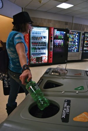 Student dropping bottle into recycling bin