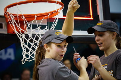 Photo: Women basketball players cutting down net.