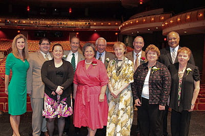 Photo: Past and present winners of the Distinguished Alumni Award pose for a photo on the Weidner Center stage.