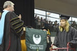 Photo: Jennifer Ulrich walks across the stage at commencement.