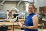 Artist Barbi Gossen in the UWGB Art Metals studio holding a piece of an alumni award