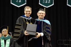 Chancellor Miller presenting Brian Sutton with a crystal mic