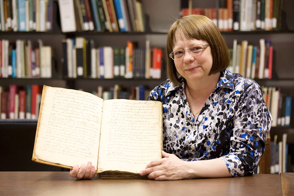 Archivist Deb Anderson poses with an original source diary.