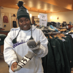 Student trying on a winter hat and mittens in the Phoenix Bookstore
