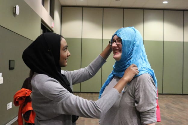 Muslim student helping another try on a Hijab
