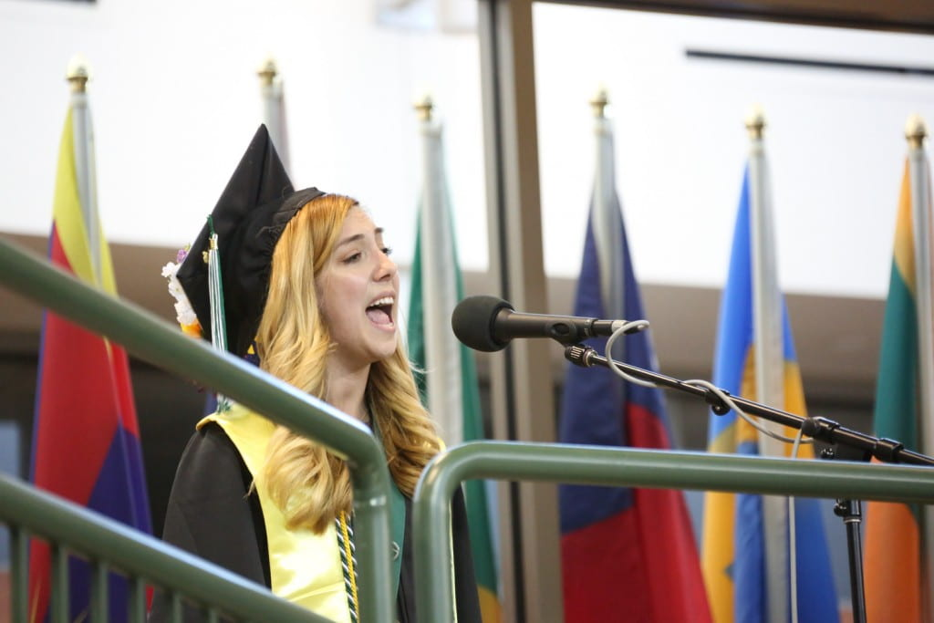 Emily Ahrens singing the national anthem at spring 2018 commencement
