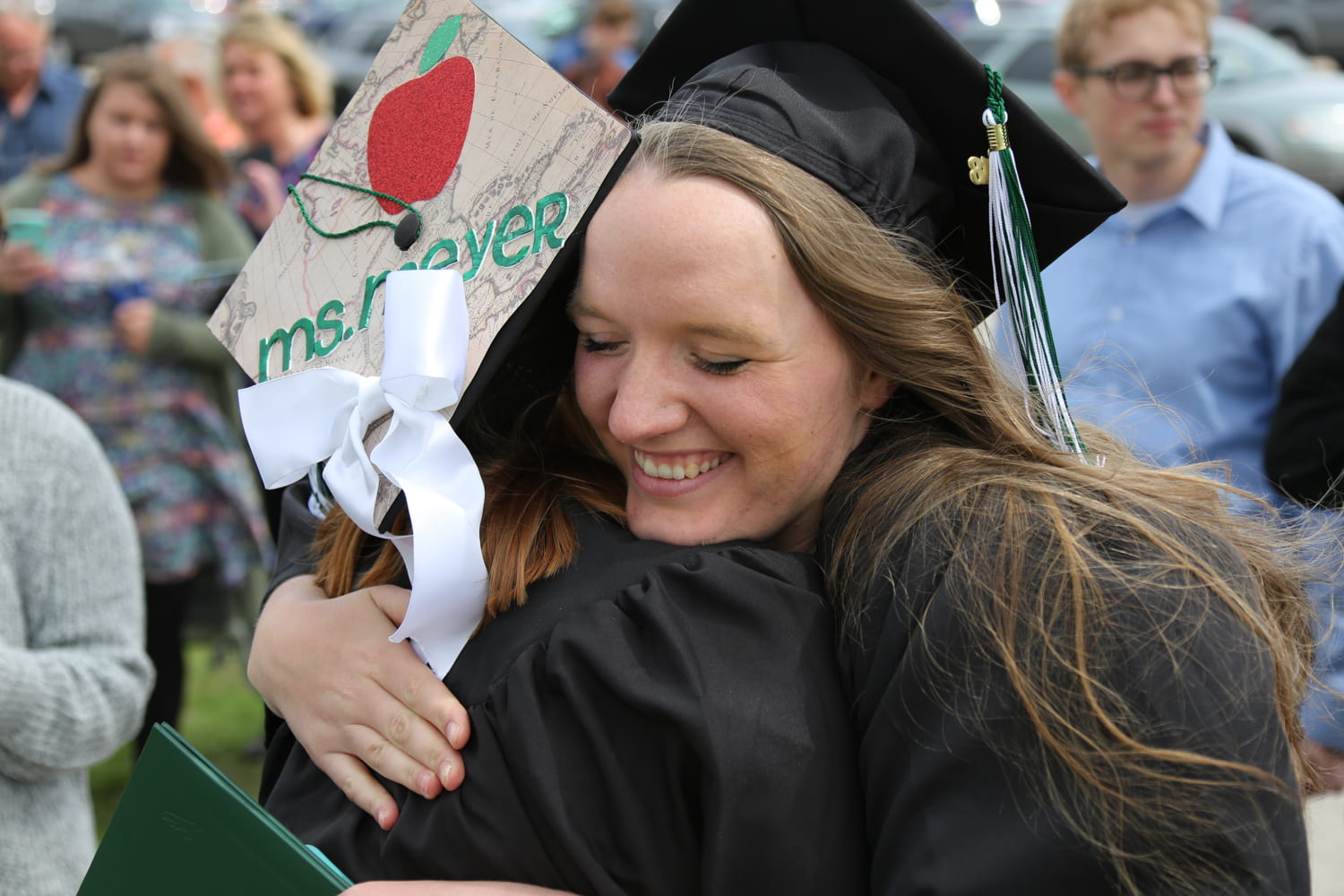 Students hug after commencement