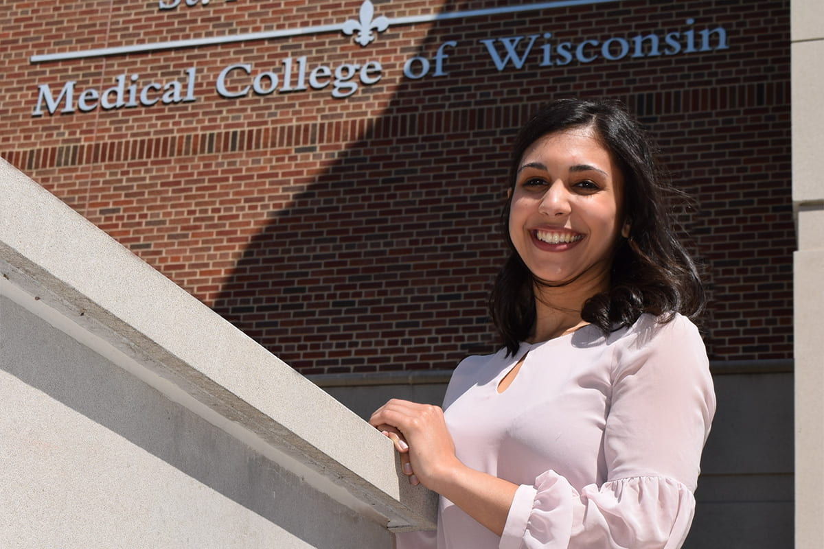 Julia Shariff standing in front of the Medical College of Wisconsin building sign
