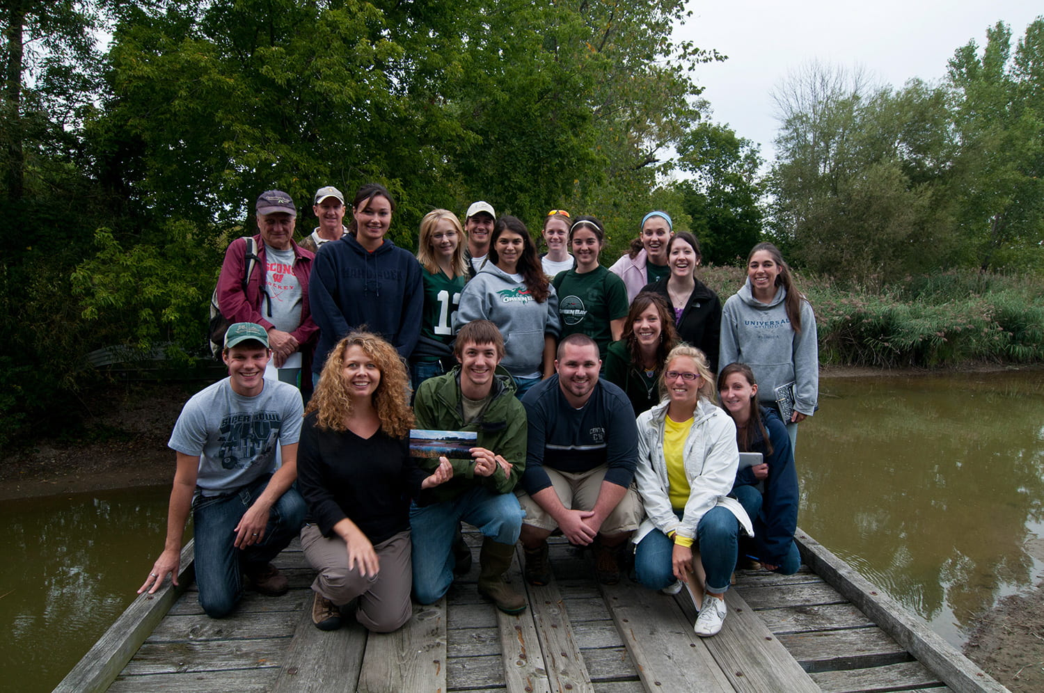 Amy Wolf posed with students by a waterway