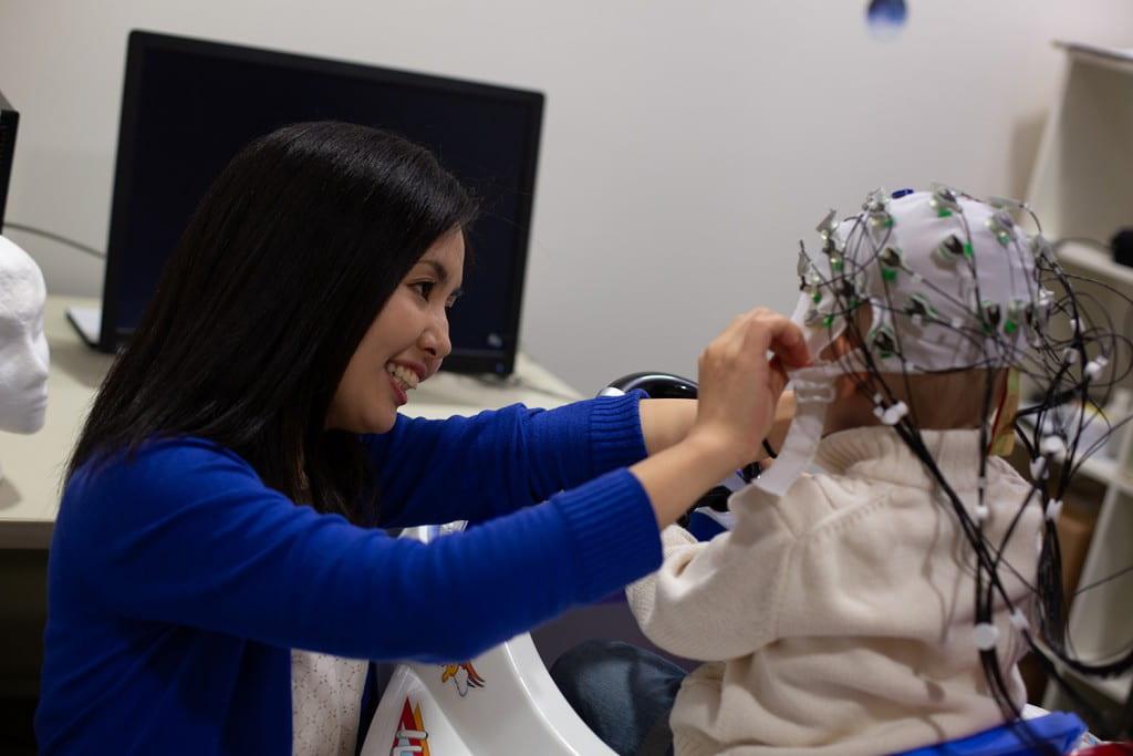 Psychology faculty Sawa Senzaki fitting subject with EEG cap