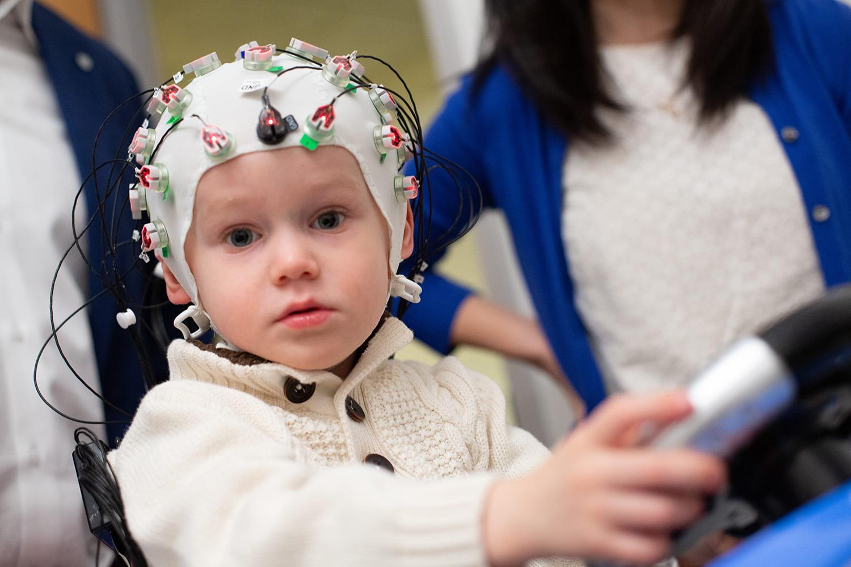Child research subject wearing EEG cap.
