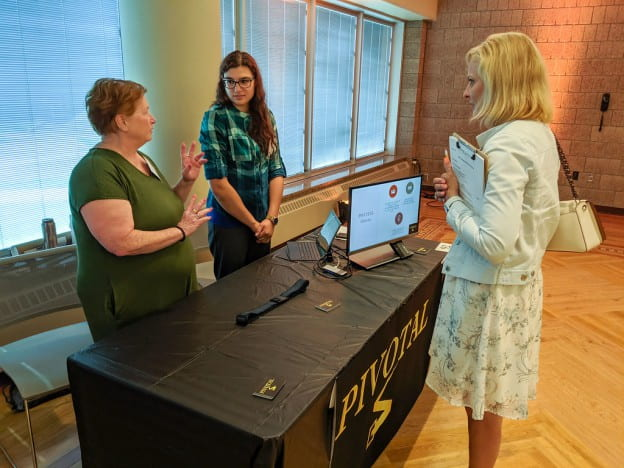 "UW-Green Bay students Carol Brehmer, left, and Ebanie Schmidt explain their innovation ""PIVOTAL""—a belt designed specifically for outdoor hobbyists and blue-collar workers—during the WiSys Innovation Showcase during WSTS at UW-Stout."