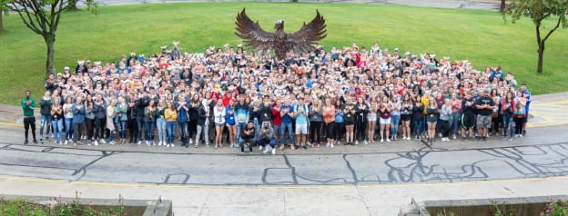 Freshmen students gather for a group photo in front of the Phoenix sculpture.