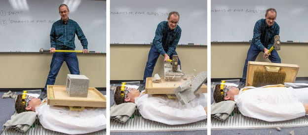 Brian Welsch smashes a block with a sledgehammer on a student lying on a bed of nails.