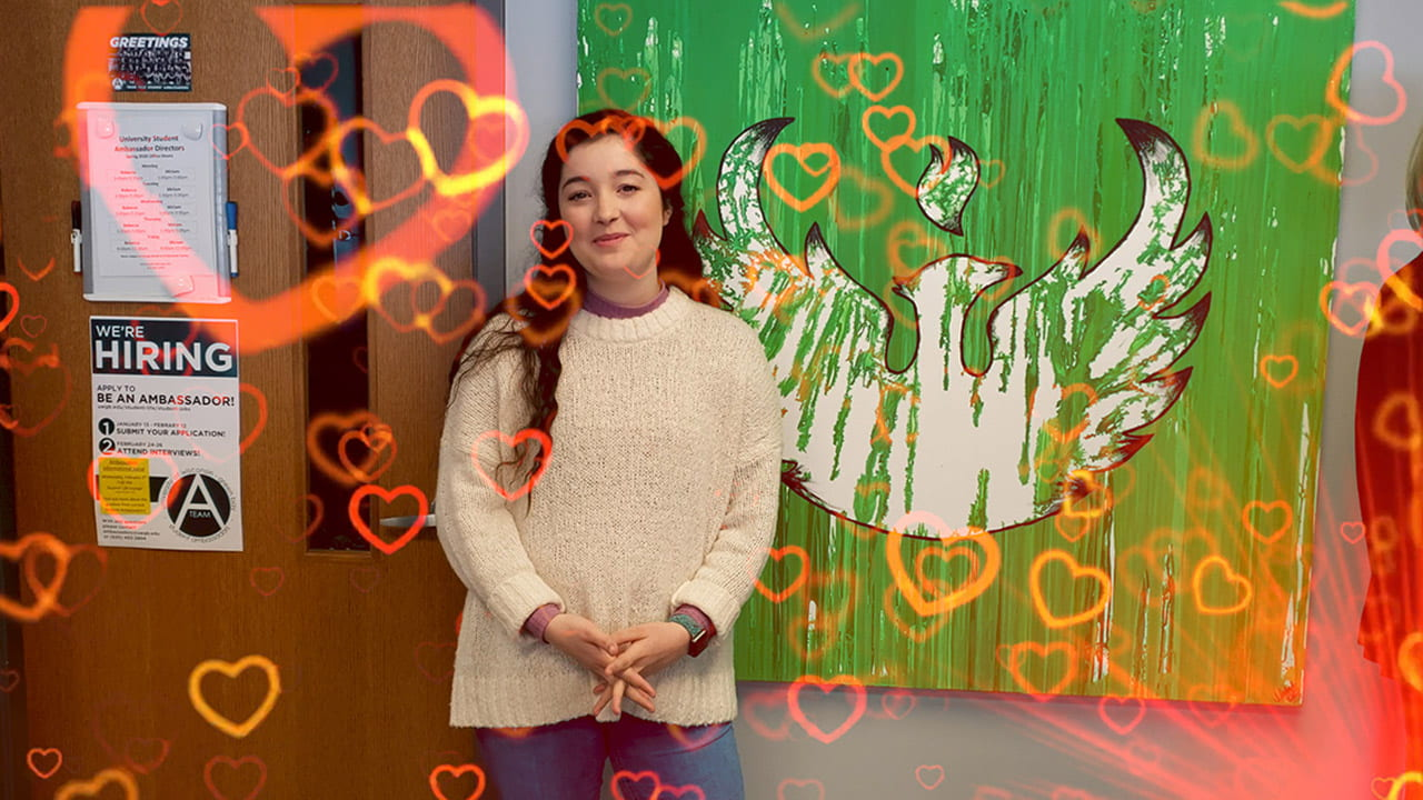 A Phoenix student standing in front of a wall painting of a Phoenix, shares what she loves about her experience on the UW-Green Bay campus.
