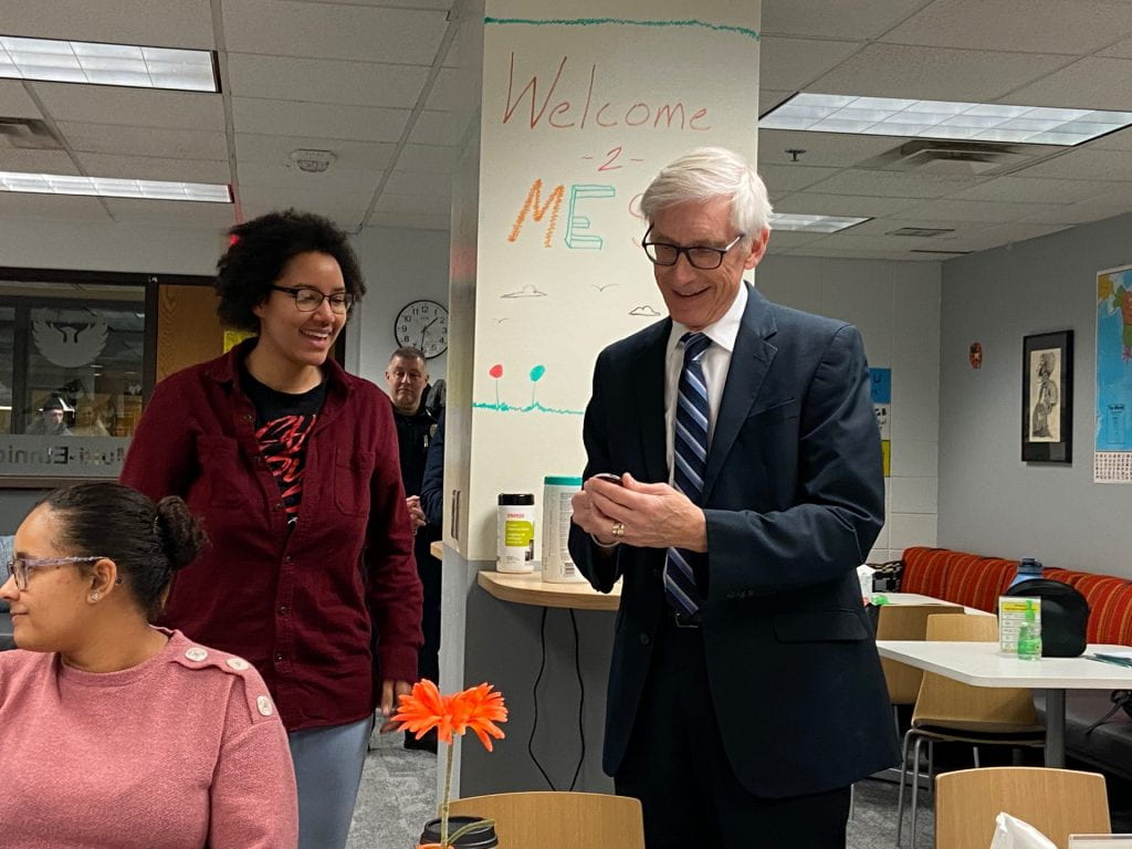Candid photo of Governor Evers and student interacting