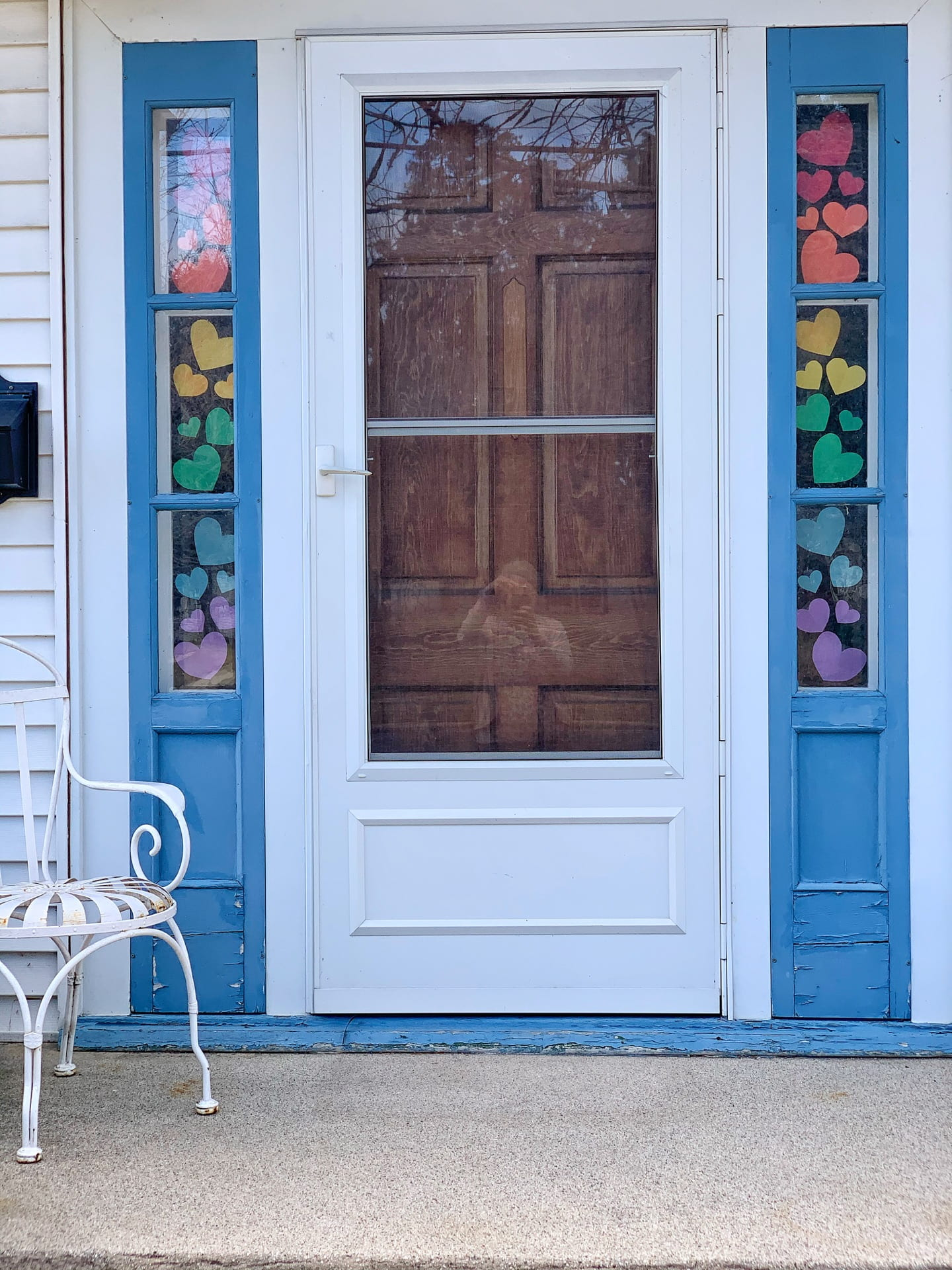Front door with colorful paper hearts taped to the side-light windows.