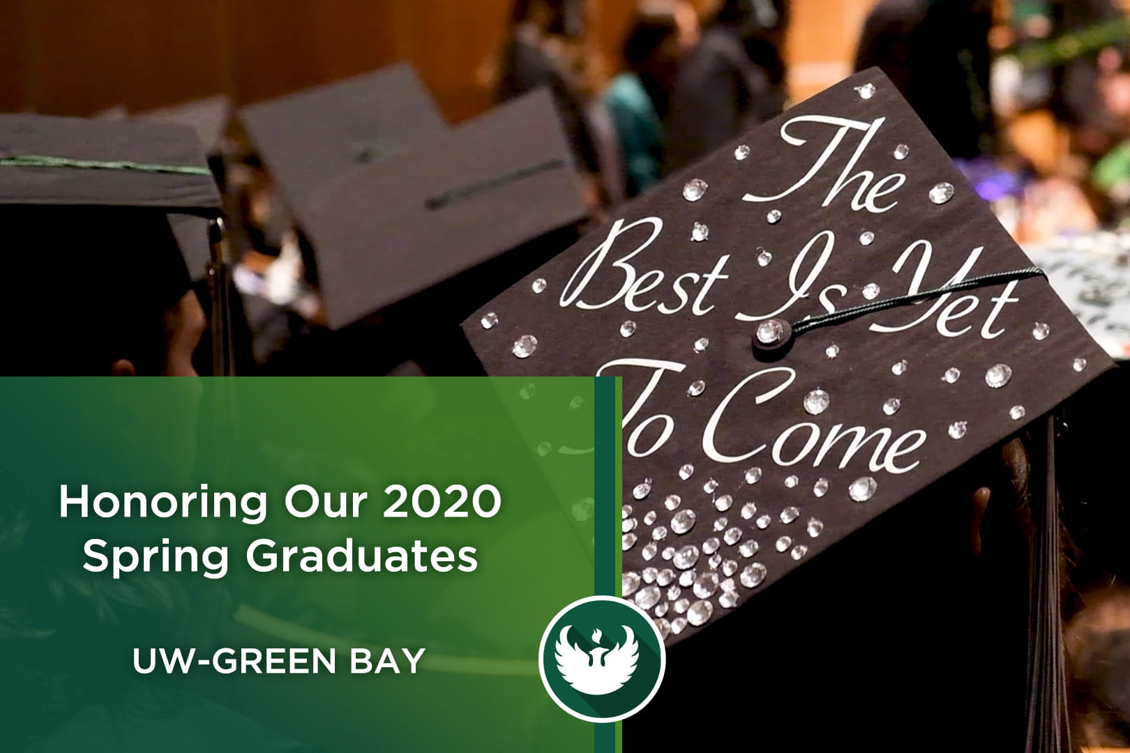 Photo of the back of a student's graduation cap as students watch other graduates receive their diploma at the UW-Green Bay Commencement ceremony.