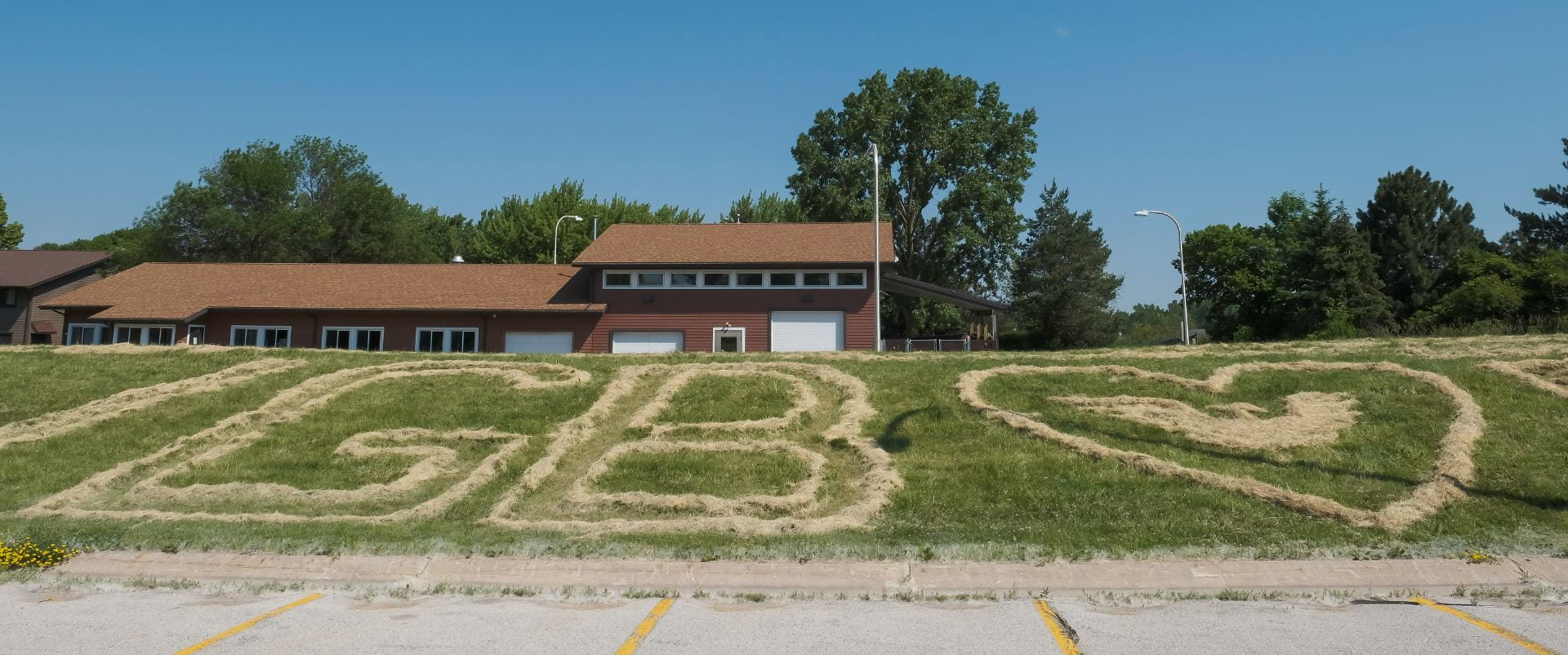 Photo of the letters GB and a large heart with a phoenix carved in the lawn at the UW-Green Bay campus.