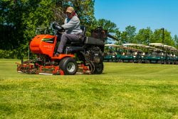 A golf course employee operates the lawn mower to get the fairway trimmed at Shorewood Golf Course.