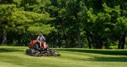 A golf course employee operates the lawn mower to get the greens trimmed at Shorewood Golf Course.