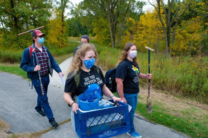 Photo of Assistant Professor Kelly Deuerling's Soil Environment students carrying soil augers and equipment for the soil testing outdoor lab in the Cofrin Memorial Arboretum on the UW-Green Bay campus.