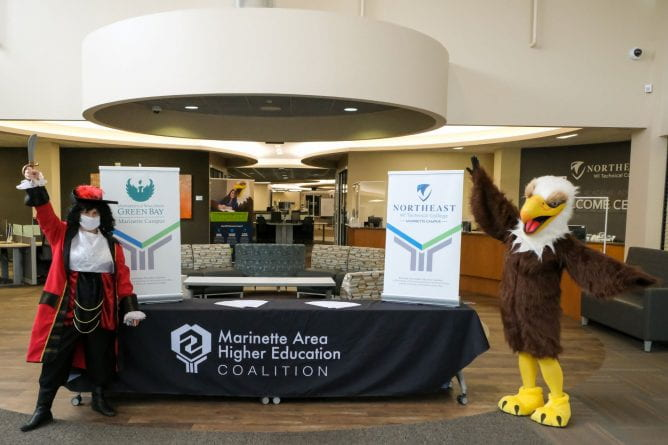 Photo of The UW-Green Bay, Marinette Buccaneer mascot, left, poses with the Northeast Wisconsin Technical College-Marinette Eagle mascot at the Marinette Area Higher Ed Coalition table.