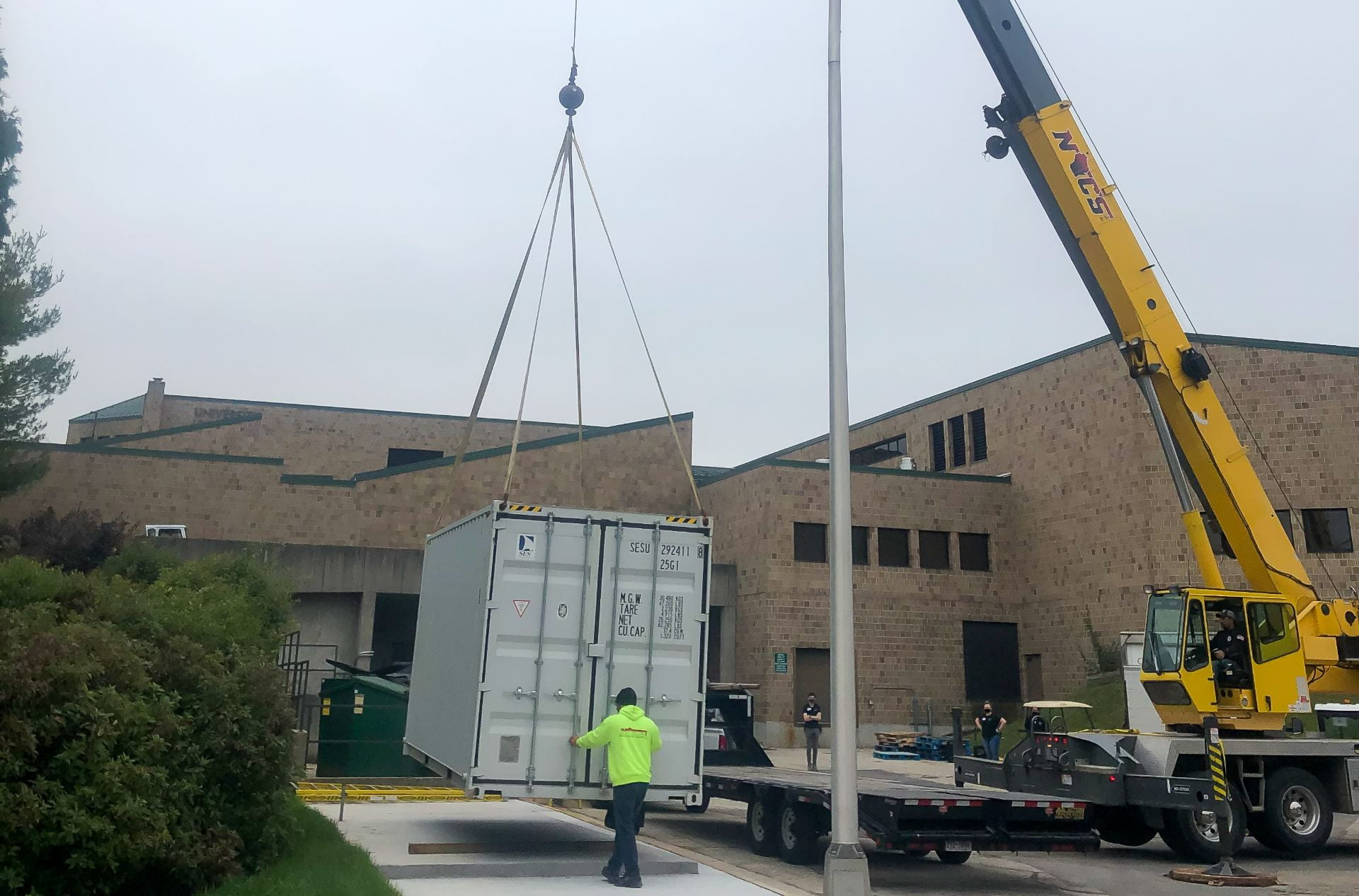 A large crane installs An Intermodal Earth Flow composting steel vessel outside the University Union delivery area.