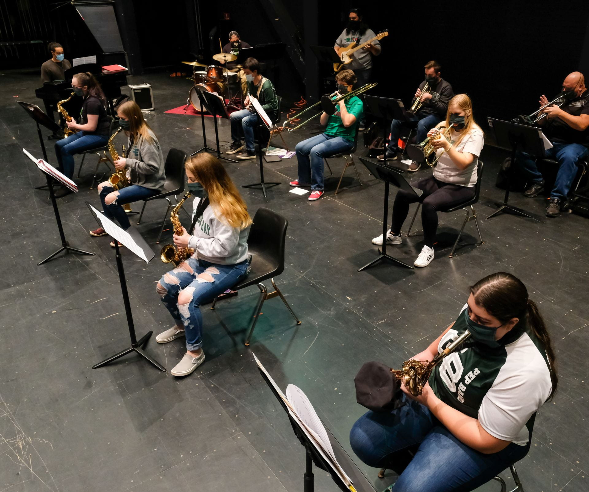 Photo of UW-Green Bay students in Jazz Ensemble class on the main stage at the Weidner Center. Music students use specialized slotted masks, bell covers on brass instruments, and sit 6-feet apart as part of the COVID-19 prevention.