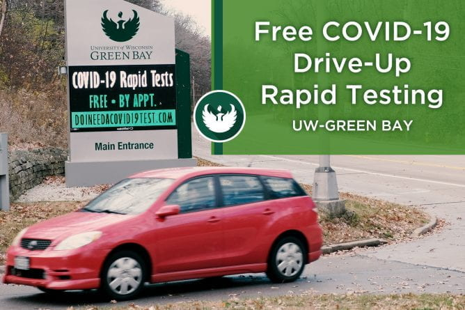 "Photo of a red car turning into UW-Green Bay's main entrance past the digital marquee with the text ""Covid-19 Rapid Test, free, by appointment doineedacovid19test.com."""