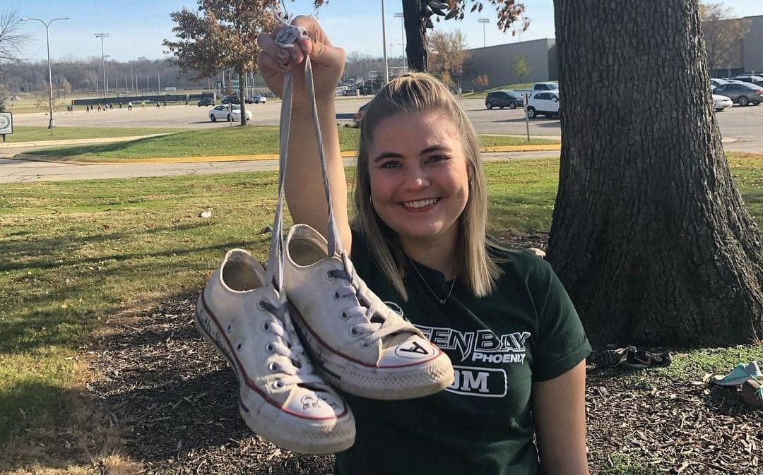 UW-Green Bay grad holding shoes in front of The Shoe Tree