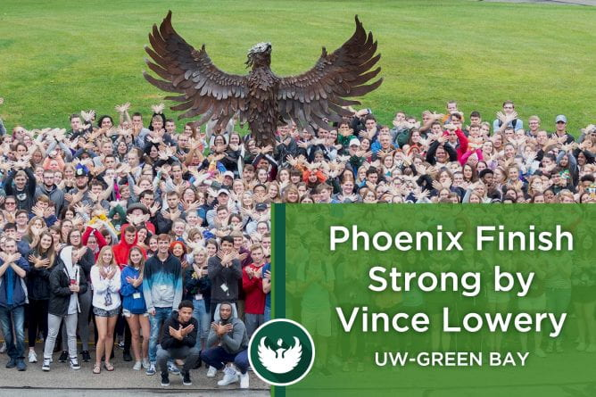 "Photo of the UW-Green Bay Phoenix sculpture with students standing in front making a hand phoenix by interlocking their hands together with the words, ""Phoenix Finish Strong by Vince Lowery."""