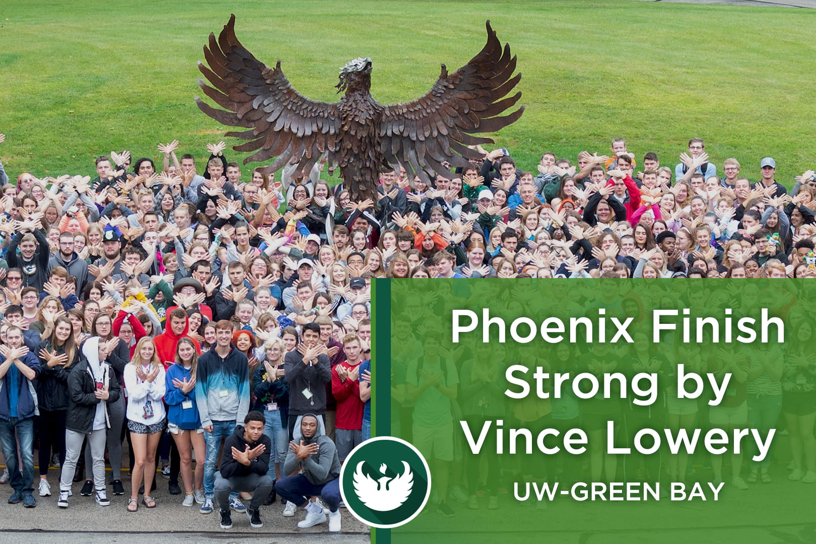 """Photo of the UW-Green Bay Phoenix sculpture with students standing in front making a hand phoenix by interlocking their hands together with the words, """"Phoenix Finish Strong by Vince Lowery."""""""
