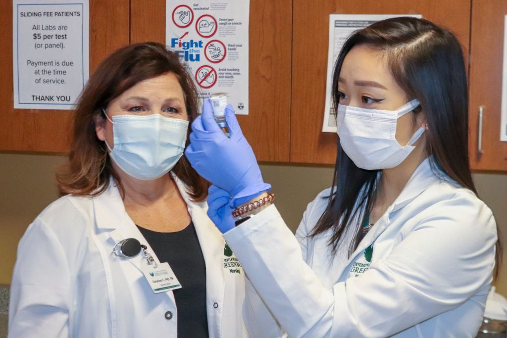UW-Green Bay Nursing student, Precious Yang draws up the Moderna COVID-19 vaccine to immunize a patient at the Lakeshore Community Health Center in Manitowoc on Friday, March 26, 2021. Observing the nursing student, left, Christine Vandenhouten, chair of Nursing & Health Studies at UW-Green Bay.
