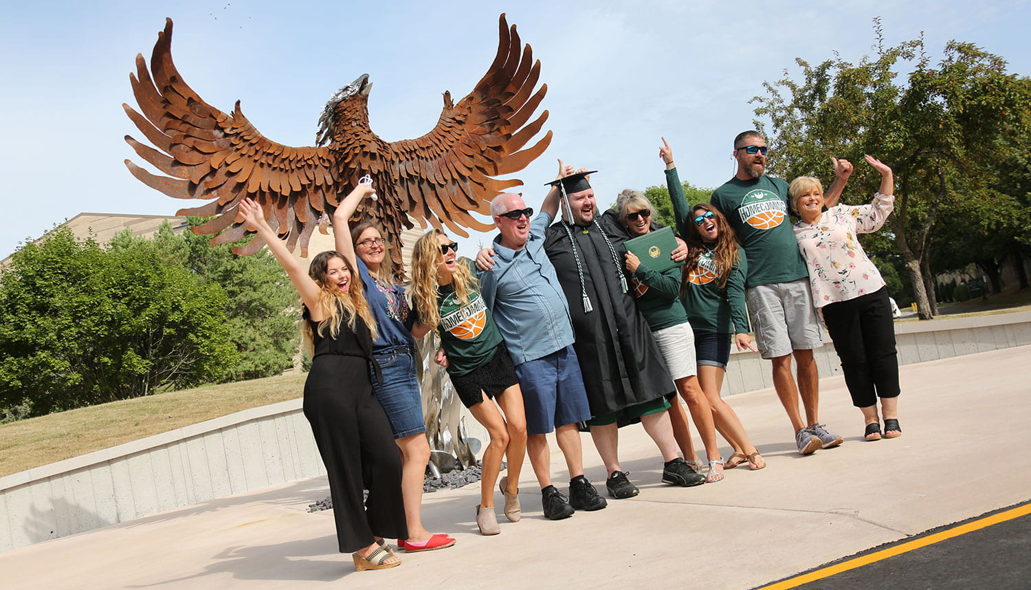 A graduate and thier guests post in front of the Phoenix sculpture.