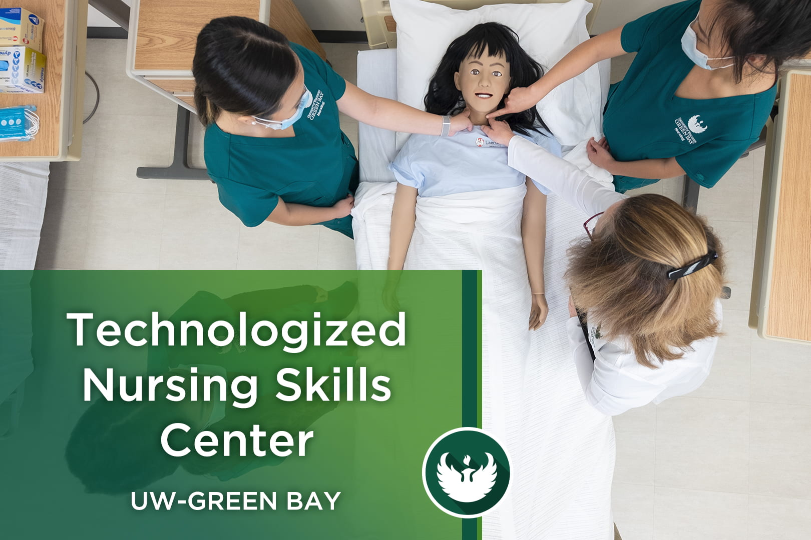 Photo from over the top of a nursing bed with two nursing students and a professor feeling the neck of a high-tech mannequin for a pulse with the text, Technologized Nursing Skills Center.