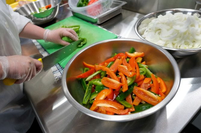 A student in Students in Quantity Food Production and Service class slices Bell peppers for the Jamaican Philly sandwiches in the Food Lab at the STEM Center.